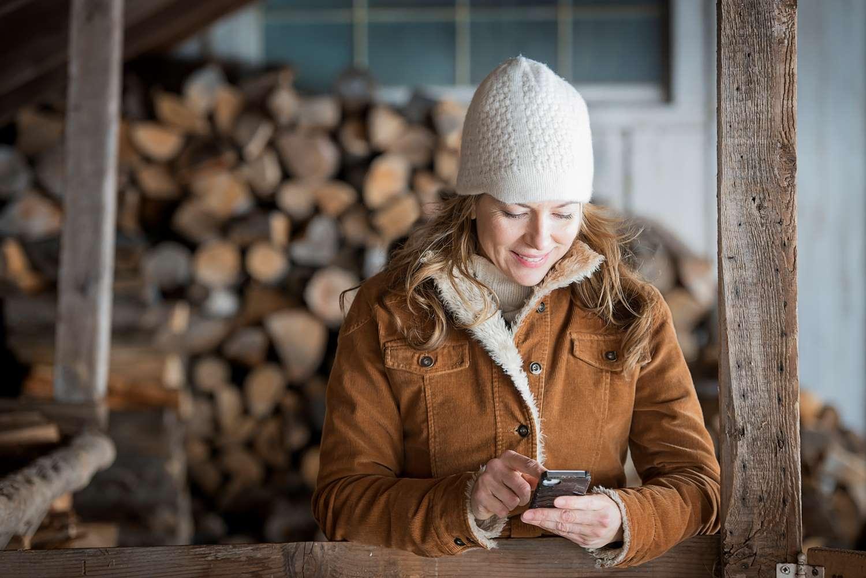 a-woman-in-sheepskin-coat-and-woollen-hat-using-a--FPN2TWN