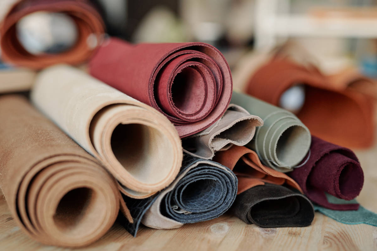 Collection of rolled suede and leather of various colors lying on wooden table