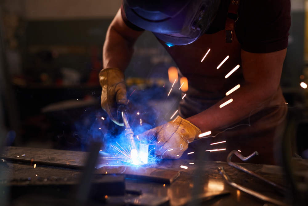 Busy workman in gloves and apron standing at metal table and binding metal details with welding