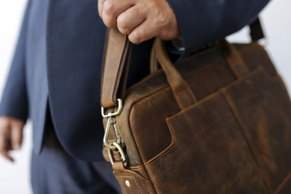 Businessman carrying his brown leather business briefcase