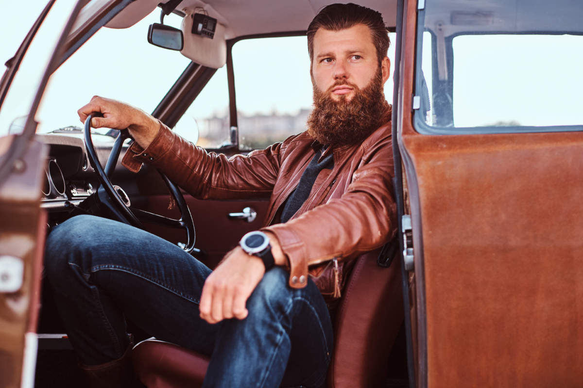 Bearded male dressed in brown leather jacket sits behind the wheel of a tuned retro car with open door.