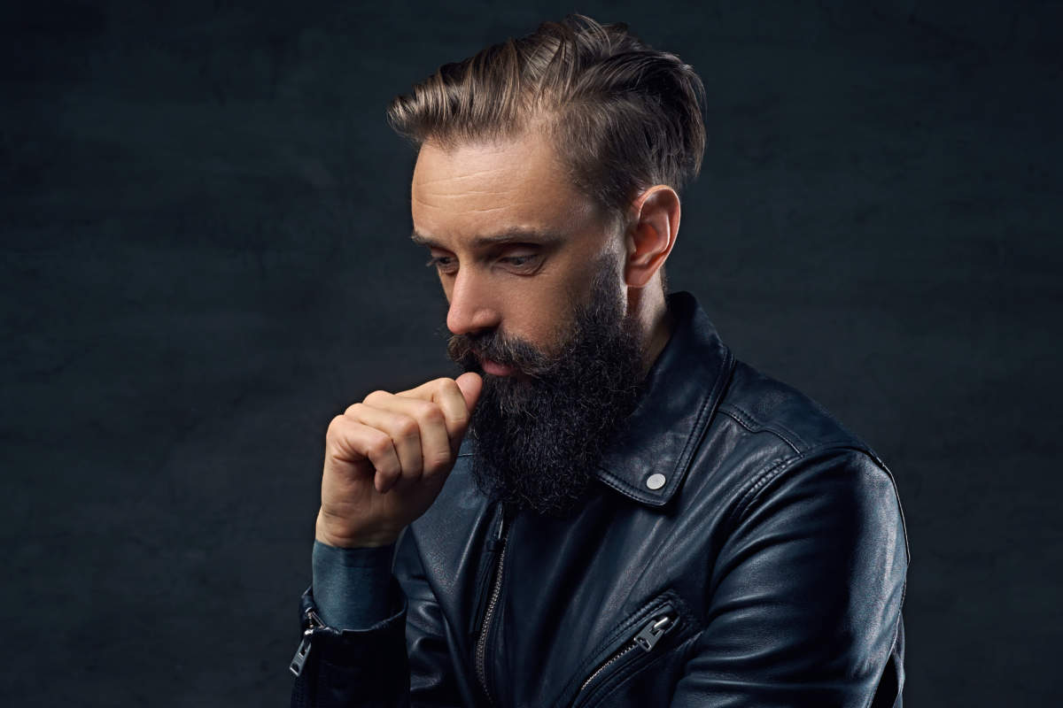 Thoughtful bearded male in a black leather jacket.