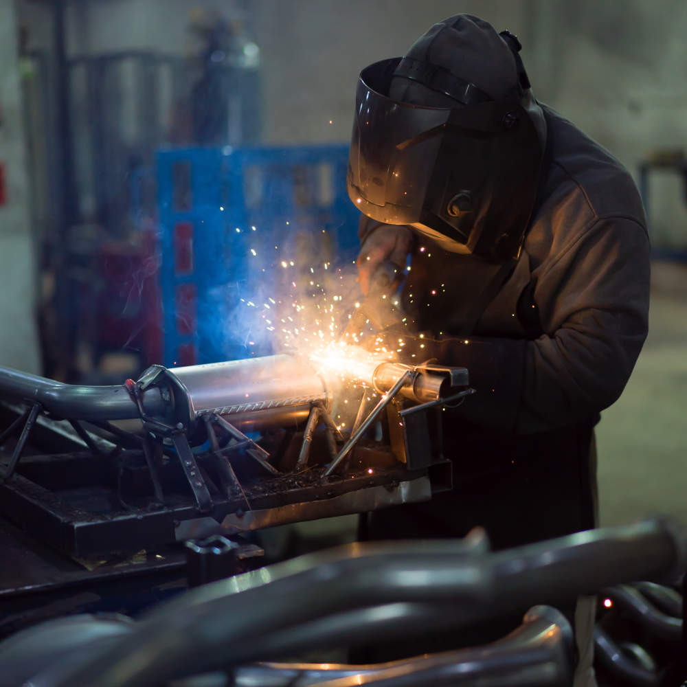 dramatic view of a worker wearing protective gear, welding together pieces of an exhaust pipe, with several other pipes around, on the work table, and metal blue frames in the background, in an industrial setting
